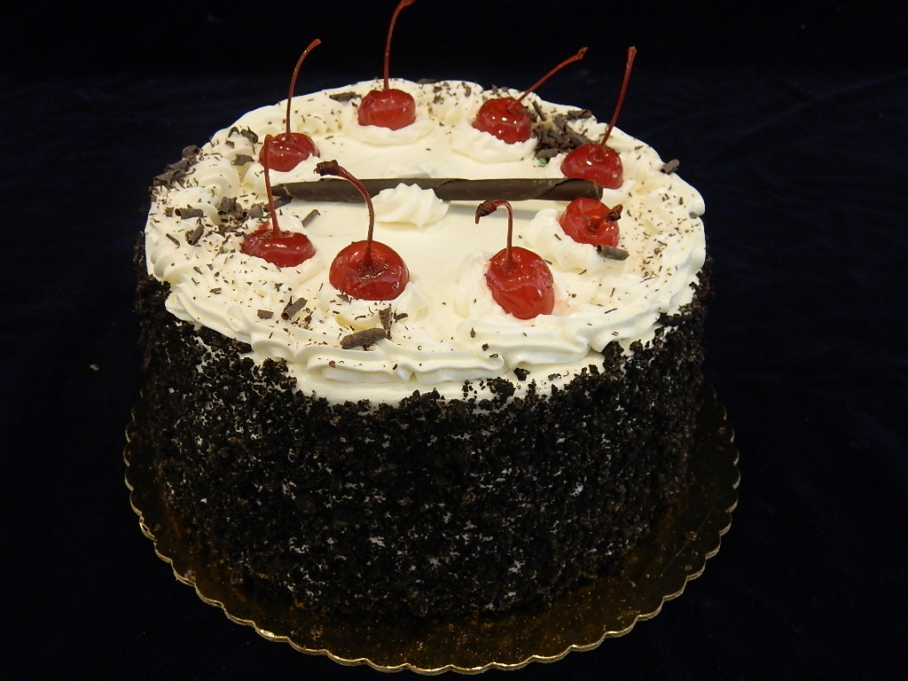 BLACK FOREST CAKE: Combination cake, filled with a classic CherryKirsch center, and topped with vanilla buttercream, chocolate shavings, and maraschino cherries.