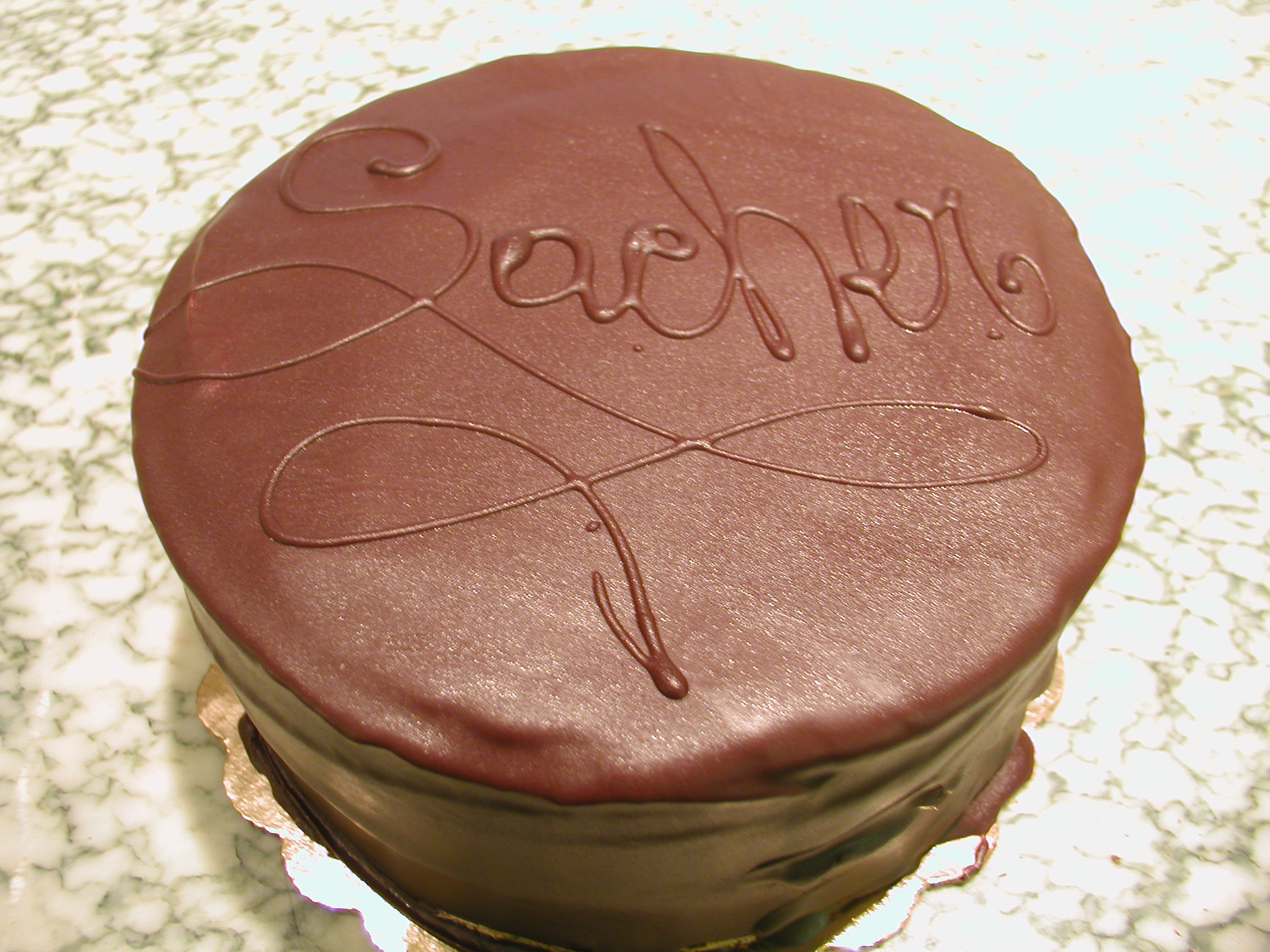 SACHER TORTE: A chocolate cake with apricot preserves between the layers, topped with a chocolate buttercream and draped chocolate ganache.